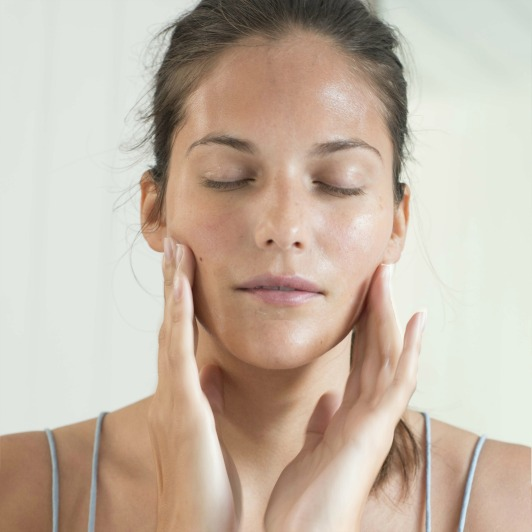 Woman massaging Cellular Recovery Skin Bliss Capsules facial oil into skin with circular motions.