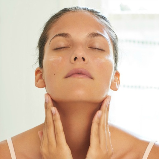 Woman applying Pro-Collagen Neck and Décolleté Balm to her neck with both hands.