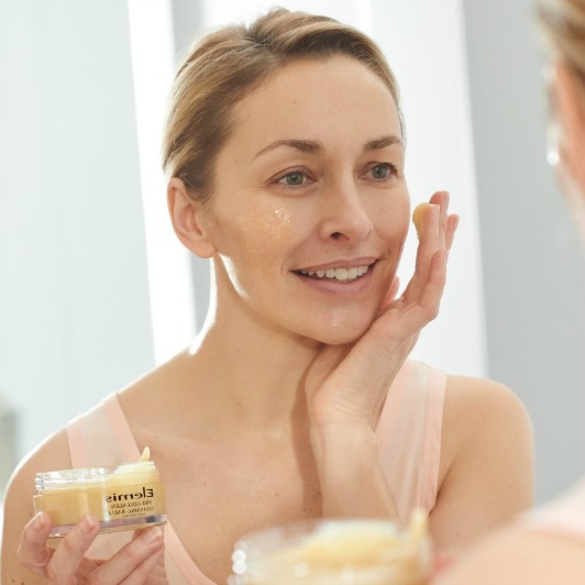 Mature woman smiling while applying ELEMIS Pro-Collagen Cleansing balm with smooth, buttery texture to face.