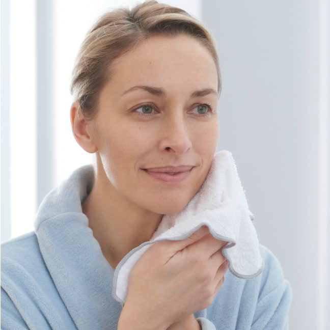 Mature woman in blue bathrobe removing Pro-Radiance Cream Cleanser from her face with soft cotton cleansing mitt
