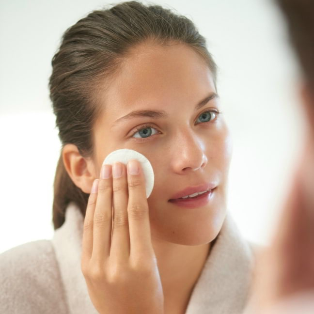 Woman cleansing her face with Balancing Lime Blossom Cleanser and wiping off the cleanser with a cotton pad.