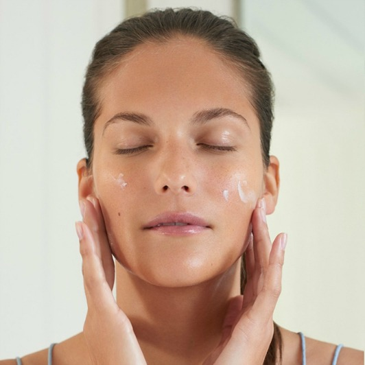 Woman massaging Papaya Enzyme Peel exfoliator cream into cheeks.