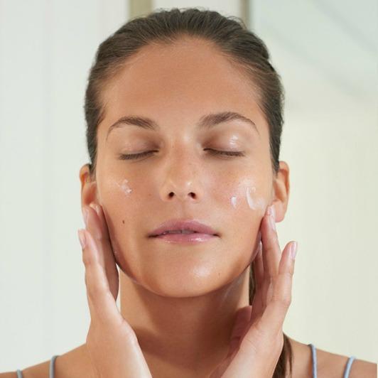 Woman massaging Papaya Enzyme Peel exfoliator cream into cheeks.