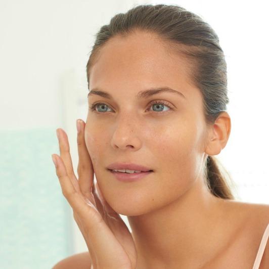Woman massaging Pro-Collagen Marine Cream Ultra Rich moisturiser into face.