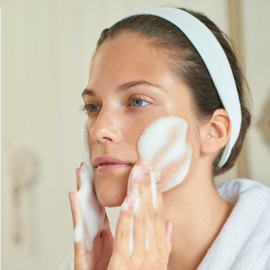 Woman applying white foam from ELEMIS White Brightening Even Tone Cleanser to face with circular motions.