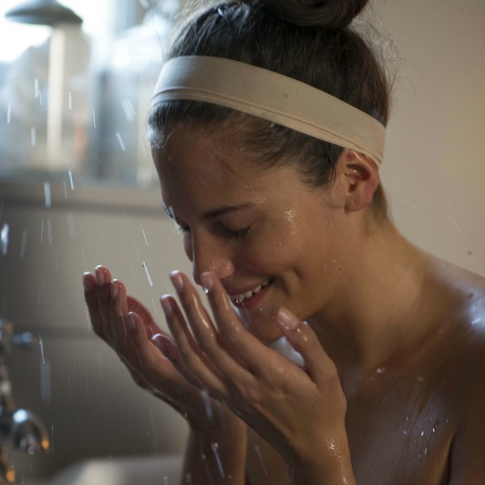 Woman smiling while rinsing her face with ELEMIS Sensitive Cleansing Wash in the shower.