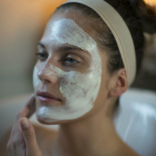 Woman applying Herbal Lavender Repair Mask to her face, avoiding the eye-area and the lips.