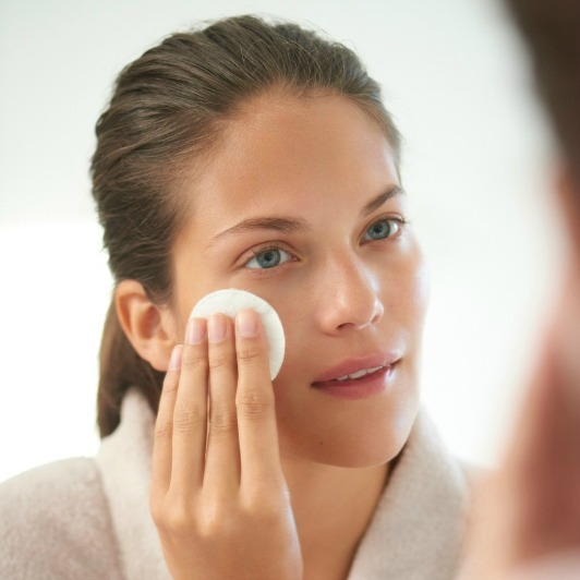 Woman in bathrobe wiping ELEMIS Balancing Lavender Toner over face with a cotton pad.